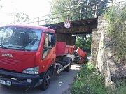 Převrácený bagr pod železničním mostem v Prostějově-Vrahovicích