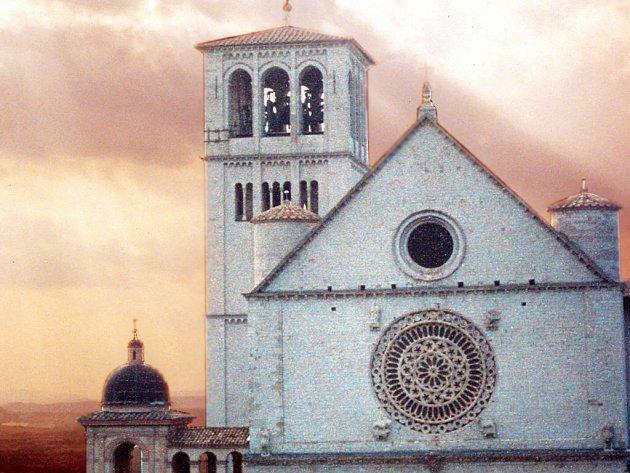 Slunce se protlouká skrze mraky nad hlavní katedrálou v Assisi.