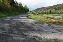 Výmoly na silnici u železničního přejezdu mezi Stražiskem a Čunínem