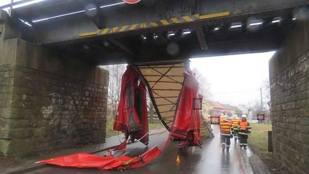 Řidič přehlédl značku o nízkém podjezdu. S vozidlem se zaklesl do mostu