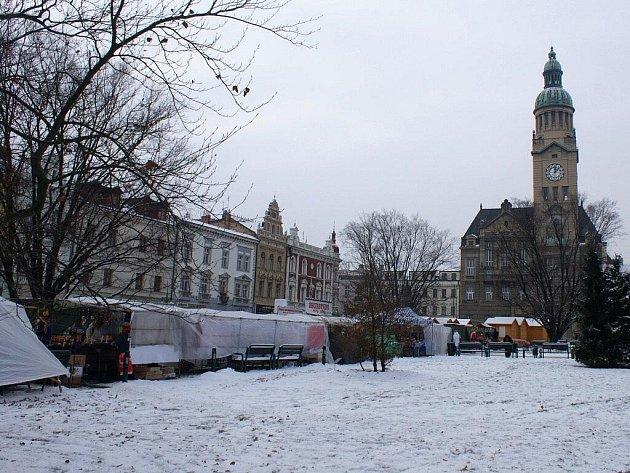 Desítku stylových dřevěných stánků na náměstí při vánočních trzích doprovázejí další jejich ne moc vkusní igelitoví kolegové