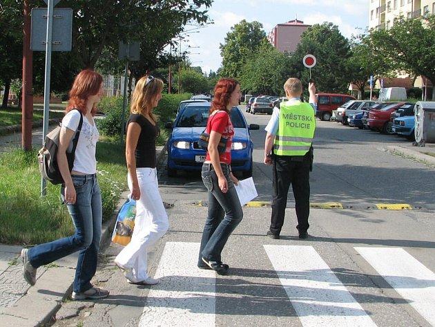 Strážníci umožňují chodcům bezpečnější přechod rušné komunikace.