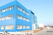 Modrou barvou zářící administrativní budova nové továrny firmy DGPack v Prostějově