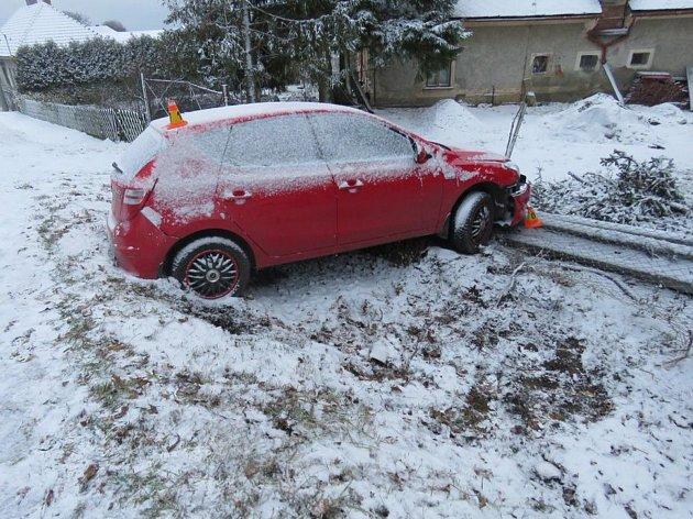 Mladá řidička podcenila zasněženou silnici. A skončila s autem v plotě