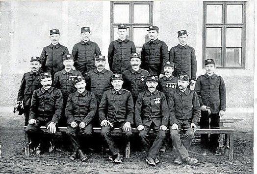 HASIČI. Sbor dobrovolných hasičů byl v obci založen v roce 1882. Dodnes je sbor aktivní a má v obci důležité postavení. Fotografie pochází z roku 1912. Hasiči stojí před starým pohostinstvím.