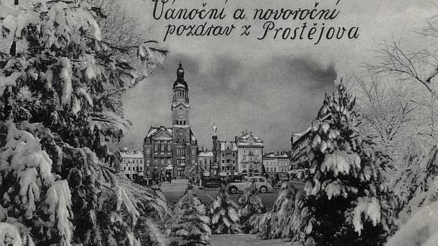 Vánoční a novoroční pozdrav zProstějova, pohlednice sdomalovanými lesními stromy a sněhem, 1930.