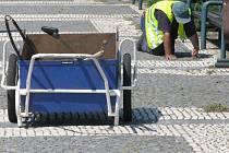 Pracovník firmy .A.S.A. čistí chodník v centrum Prostějova od trávy.