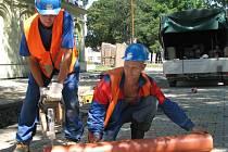 Stavební dělníci v montérkách a přilbách to nemají pod rozpáleným sluncem jednoduché.