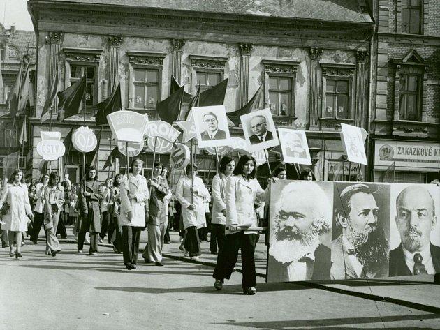Účastníci průvodu s transparenty a podobiznami komunistických model – Marx, Engels, Lenin, v pozadí Brežněv a Husák.