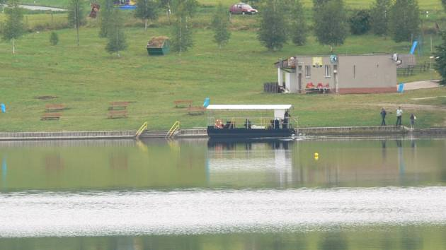 PAX 18 do nádrže aplikuje osádka speciální loďky. Hladinu přehrady brázdí už od pondělí.