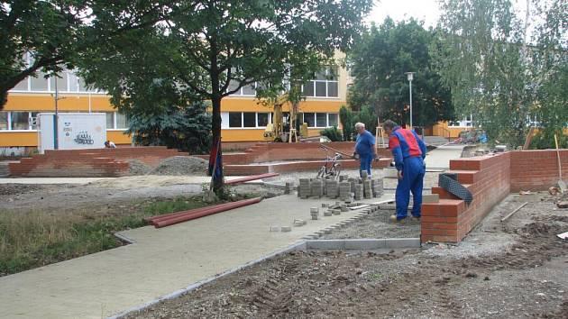 Před opravenou školou upravují řemeslníci také prostor malého parčíku.