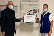 Zástupce Moravské vodárenské ředitel regionu Prostějov Jiří Suchánek předává darovací šek primáři Anesteziologicko-resuscitačního oddělení Martinu Pomajbíkovi.