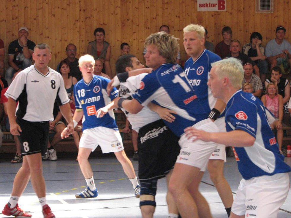 Kapitán kosteleckých házenkářů David Ševčík (uprostřed) se prodírá obranou Polanky v odvetném barážovém duelu o první ligu mužů.