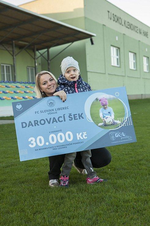 Fotbalové kluby FC Slovan Liberec a TJ Sokol Klenovice pomáhají handicapované holčičce z Prostějova. Maminka Kateřina Piňosová s dcerou Lexinkou a šekem.