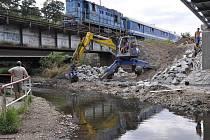 Dělníci upravují okolí nového mostu přes Hloučelu, úprav se dočká i stávající stezka kolem této říčky