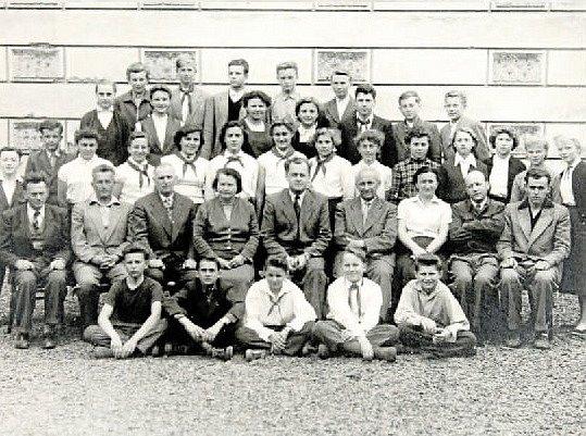 TŘÍDA 8. A v roce 1958. Osmá třída kostelecké základní školy spolu s kantory. Uprostřed sedí třídní učitel Zdeněk Navrátil, po jeho levici ředitel školy Jaroslav Kašpárek.
