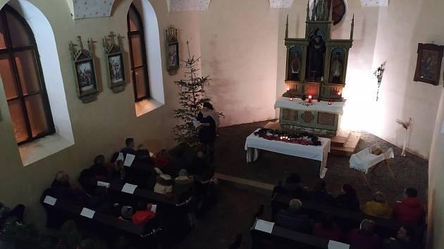 Vánoční setkání lidí u kaple v Bělé u Malont.