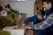 Se stavbou Velešínského betléma pomáhají zemědělci Pavlu Rouhovi také jeho synové. Na snímku je se svým zručným otcem desetiletý Pepča.
