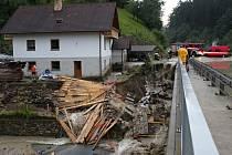 Voda s bahnem valící se v sobotu odpoledne dolů rájovským kopcem tady poškodila silnici, most i vedle stojící dům.