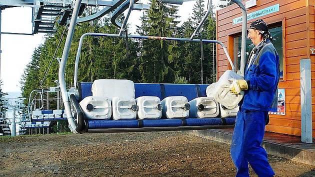 Pracovník Skiareálu Lipno Hubert Hoffmann nakládá barely naplněné pískem na lanovku Lipno Express.