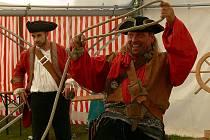 Jak je ze snímku vidět, během přídoslké pouti se bavili nejen přihlížející a návštěvníci, ale i sami účinkující, tady Bratři z Růže. Na snímku vlevo vystavený přídolský poklad.