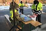 Policisté předávají roušky na hraničních přechodech.