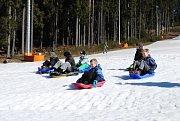 Trička s krátkým rukávem, koloběžky, kola, zimní bundy, parta dětí na bobech, tatínek s dcerkou na lyžích... Zimní sezóna na Lipně skončila před týdnem, ale půl metru sněhu na sjezdovce ladem neleží.