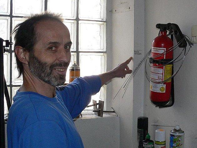 Stojící Pavel Pazderka ukazuje rysku na zdi prodejny, ve které pracuje.