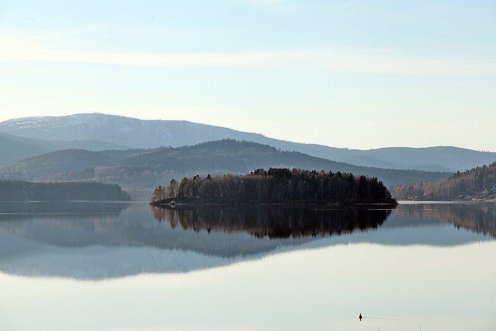 Krásné pohledy na Lipno jsou z kempu Jestřábí v Černé v Pošumaví - rozlehlá vodní plocha s ostrovem v pozadí a nad nimi se tyčící nejvyšší vrchol Šumavy - Plechý.