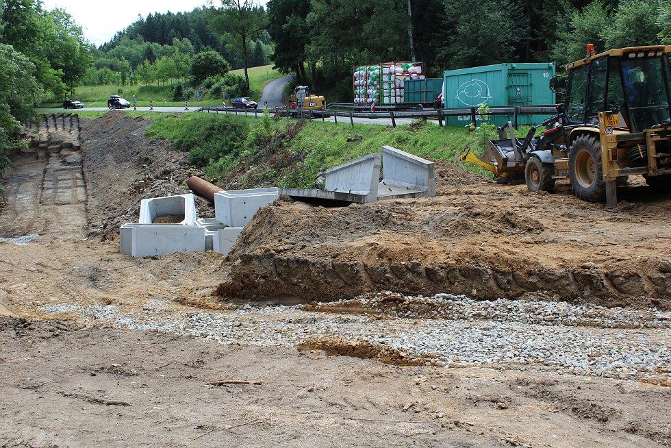 Kolem silnice a vodoteče pod ní se odehrávají náročné zemní práce.
