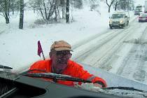 Josef Bubela čistí stěrače sypače od navátého sněhu.