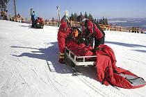 Záchranáři při ošetřování ženy, která se vážně zranila 24. února na sjzedovce lipenského ski areálu předtím, než ji předali letecké záchranné službě.