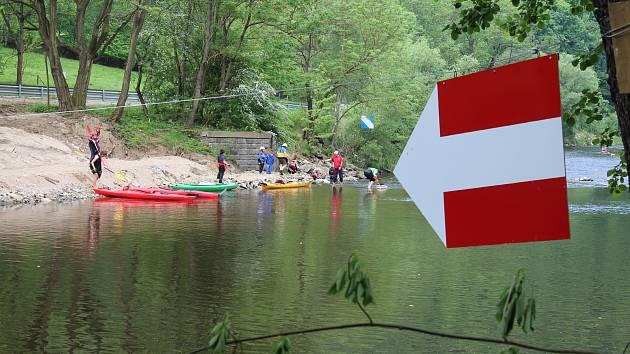 Zákaz proplutí vlevo. Dvěma bílými šipkami na červeném poli je na řece vymezené místo, kudy se nesmí proplouvat. Povoleno to je pouze u levého břehu.