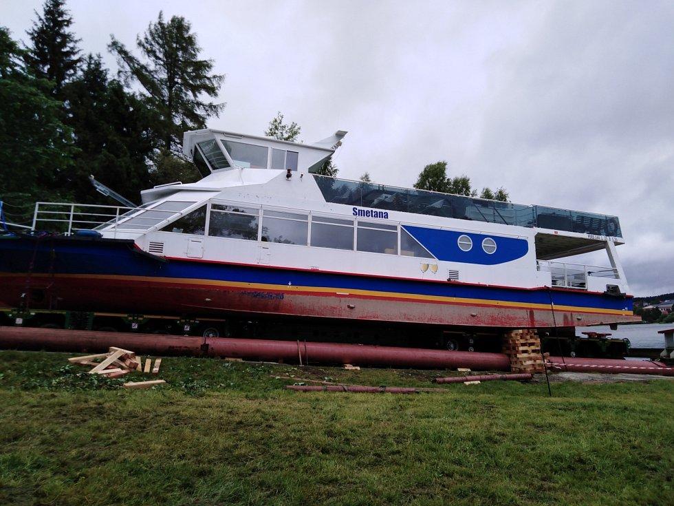 Chystá se nasunutí lodě z traileru na kozlíky, na nichž se po plechových skluzech spustí na vodu.