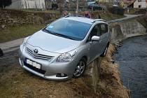 Toyota zůstala viset na potokem Polečnice v Nových Dobrkovicích. Foto: HZS Jihočeského kraje