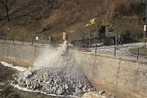 Do Vltavy navážejí nákladní auta kamení. Budují si cestu k jezu.