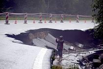 Voda s bahnem valící se dolů rájovským kopcem tady poškodila silnici, most i vedle stojící dům.