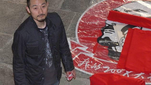 Jeden z mladých čínských výtvarníkůTian Yonghua během včerejší instalace svých děl. Podoba výtvarníka s mužem na obraze není náhodná.