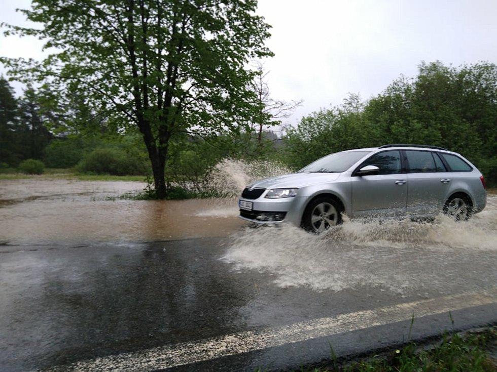 Voda z rozvodněného potoka zaplavila v neděli odpoledne při vydatném dešti silnici mezi Českým Krumlovem a Frymburkem poblíž obce Světlík.