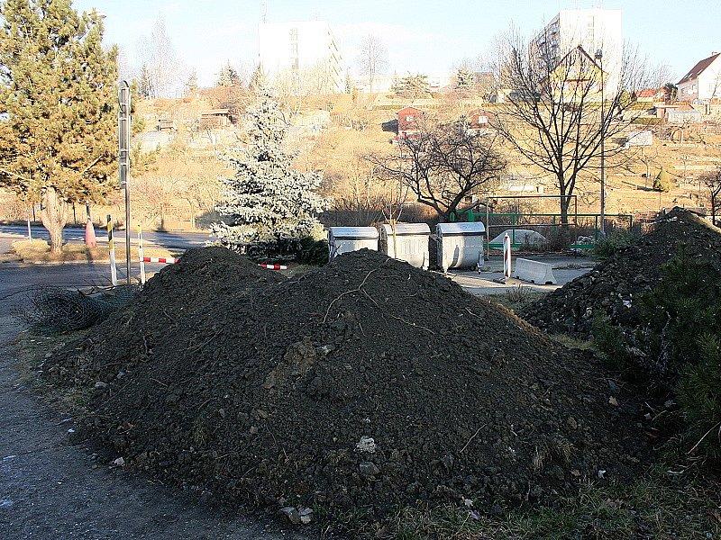 Kubíky hlíny zasypaly trávníky v okolí domu.