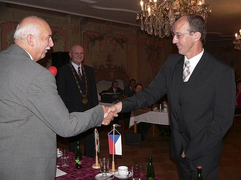 Dalibor Carda byl právě zvolen novým starostou města a Karel Vachta mu blahopřeje a předává vedení zastupitelstva.
