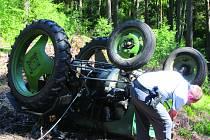 Traktor se na lesním svahu převrátil.
