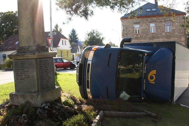 Po srážce s osobním autem  skončil poštovní vůz na boku.