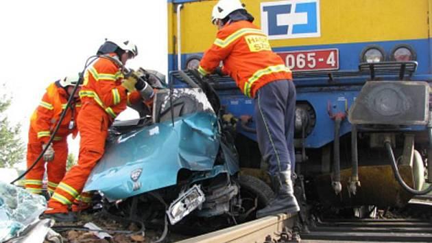 Vyproštění šoféra i vozidla zpod vlaku dalo hasičům pořádnou práci.