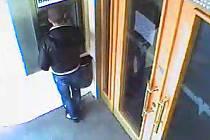 Podezřelý pachatel při manipulaci u bankomatu.