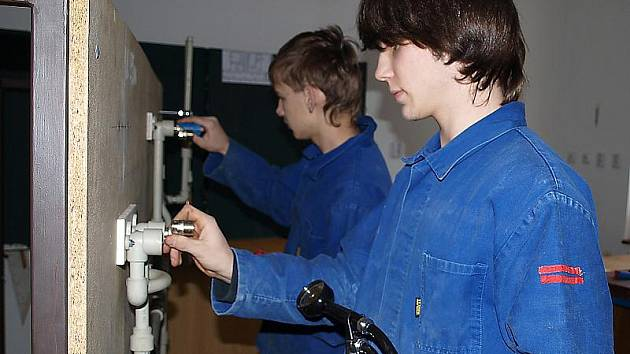 Patrik Kollinger (v popředí) a Pavel Horst, učni v oboru instalatér, při cvičné kompletaci rozvodů vody.