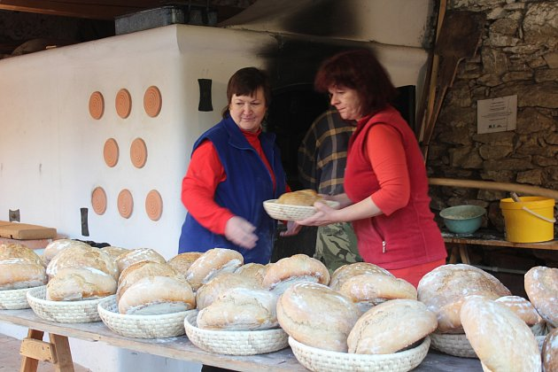 Členové spolku přátel Velešína vytahují z pece čerstvě upečený chléb.