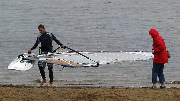 """Zatímco Lubomír Čuhel (vlevo) si u lipenského jezera počasí o víkendu pochvaloval, jeho matka (vpravo) byla jiného názoru:  """"Pro mne je zima už jenom, když ho vidím,"""" okomentovala jízdy surfařů v Černé v Pošumaví."""