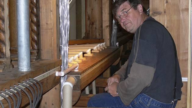 Takto vypadá interiér varhan těsně před tím, než se do něj znovu nastěhují píšťaly. Šedivé svazky nejsou kabely, ale olověné trubky, kterými se po nástroji rozhání vzduch. Na snímku varhanářský mistr Antonín Kadeřábek.