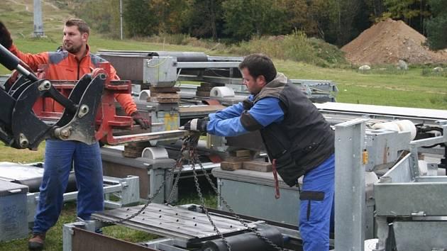 Pracovníci připravují pojízdný koberec dětského výukového hřiště Foxpark k instalaci na svah.